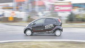 Der Peugeot iOn in Kurvenfahrt: Er rollt auf schmalem Reifen und hat zwei Steckdosen, der Motor sitzt über der Hinterachse. Bild: Ulrich Metz